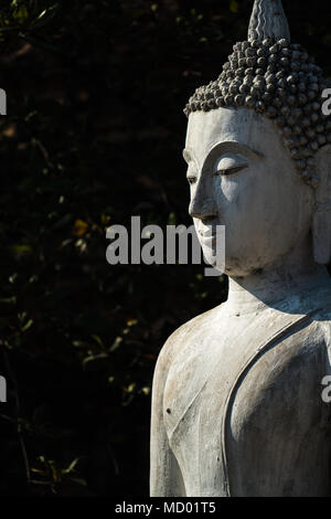 Old cement Buddha image in light and shadow in Ayutthaya Buddhist ruined temple, travel destination - Stock Photo