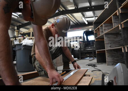 180302-N-MS236-0005 KWAJALEIN, MARSHALL ISLANDS (March 2nd, 2018) Equipment Operator 3rd Class Brady Northlee, assigned to Naval Mobile Construction Battalion (NMCB) 11, Construction Civic Action Detail Marshall Islands, measures wood to ensure accurate cuts are made for new cabinets to be placed in the warehouse. NMCB-11 is forward deployed to execute construction, humanitarian and foreign assistance, and theater security cooperation in the 7th Fleet area of operations. (U.S. Navy photo by Construction Electrician 2nd Class Joshua Zapien) - Stock Photo