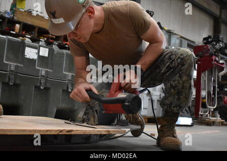 180302-N-MS236-0008 KWAJALEIN, MARSHALL ISLANDS (March 2nd, 2018) Equipment Operator 3rd Class Brady Northlee, assigned to Naval Mobile Construction Battalion (NMCB) 11, Construction Civic Action Detail Marshall Islands, cuts plywood for warehouse shelving, improving the overall functionality of the material storage warehouse. NMCB-11 is forward deployed to execute construction, humanitarian and foreign assistance, and theater security cooperation in the 7th Fleet area of operations (U.S. Navy photo by Construction Electrician 2nd Class Joshua Zapien) - Stock Photo