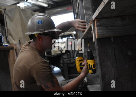 180302-N-MS236-0012 KWAJALEIN, MARSHALL ISLANDS (March 2nd, 2018) Constructionmen Stephen Cheshire, assigned to Naval Mobile Construction Battalion (NMCB) 11, Construction Civic Action Detail Marshall Islands, fastens dividers for new shelving in the material storage warehouse. NMCB-11 is forward deployed to execute construction, humanitarian and foreign assistance, and theater security cooperation in the 7th Fleet area of operations. (U.S. Navy photo by Construction Electrician 2nd Class Joshua Zapien) - Stock Photo