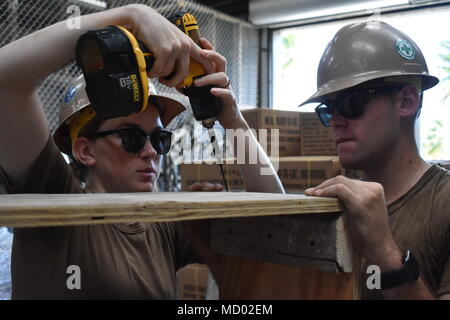 180306-N-MS236-0003 KWAJALEIN, MARSHALL ISLANDS (March 6th, 2018) Constructionman Jessika Corwin, left, and Constructionman Stephen Cheshire, assigned to Naval Mobile Construction Battalion (NMCB) 11, Construction Civic Action Detail Marshall Islands, assemble new cabinets for medical supply storage to enable more efficient use of the space. NMCB-11 is forward deployed to execute construction, humanitarian and foreign assistance, and theater security cooperation in the 7th Fleet area of operations. (U.S. Navy photo by Construction Electrician 2nd Class Joshua Zapien) - Stock Photo
