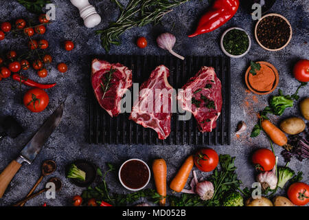 top view of raw meat slices and vegetables on black concrete surface - Stock Photo