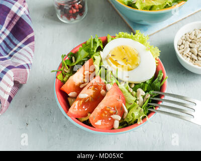 Salad with tomatoes and eggs in a light ceramic plate. - Stock Photo