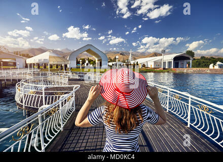 Tourist woman in red Hat and striped dress walking down the pier in Ruh Ordo cultural complex Issyk Kul lake with mountains background at sunset in Ch - Stock Photo