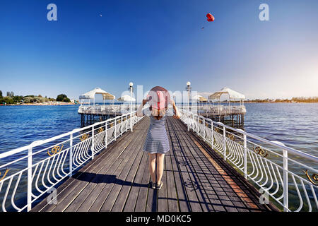 Tourist woman in red Hat and striped dress Standing down the pier in Ruh Ordo cultural complex Issyk Kul lake with mountains background at sunset in C - Stock Photo
