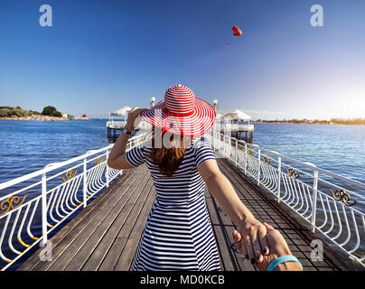 Woman in red Hat and striped dress holding his boyfriend by hand and walking to the pier in Ruh Ordo cultural complex at Issyk Kul lake with mountains - Stock Photo
