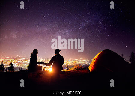 Happy couple in silhouette sitting near campfire and orange tent. Night sky with milky way stars and city lights at background. - Stock Photo