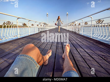 Woman in striped dress with red hat going to his boyfriend by on the pier in the beach - Stock Photo