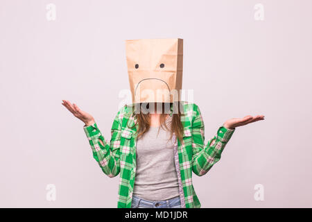 Unhappy girl with sad emoticon on paper bag on her head on white background - Stock Photo