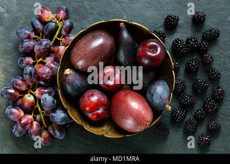 Dark Exotic Fruits on slate background including passion fruit, plums, figs, grapes, black berries - Stock Photo