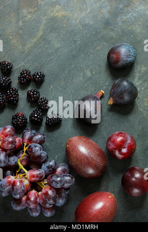 Dark Exotic Fruits on slate background including passion fruit, plums, figs, grapes, black berries, with copy space - Stock Photo