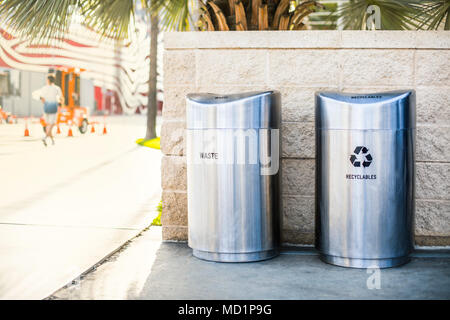 Separate garbage bins for recycled trash and waste installed on a sidewalk on the city street - Stock Photo