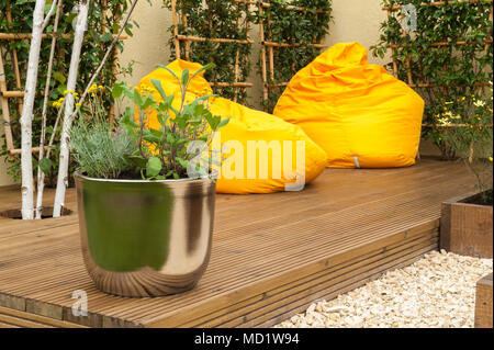 Close-up of pot plants & bright colourful, yellow beanbag chairs on timber decking - 'The Journey Garden' - RHS Flower Show, Tatton Park, England, UK - Stock Photo