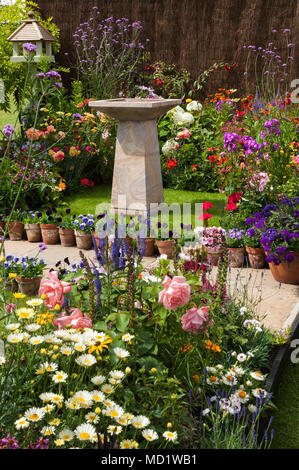 Bright colourful summer flowering plants on borders, path & stone birdbath - English cottage garden display, RHS Flower Show, Tatton Park, England, UK - Stock Photo