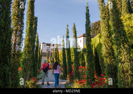 Granada, Andalusia, Spain - October 7th, 2012 : Tourists walk through the colourful gardens of the Generalife, within the Alhambra and Generalife comp - Stock Photo