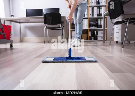 Janitor's Hand Cleaning Floor With Mop At Workplace - Stock Photo