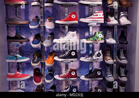 Converse trainers and Vans shoes in shop display - Stock Photo