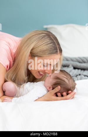 young, beautiful and blond mother with pink shirt is cuddling with her baby in bed - Stock Photo