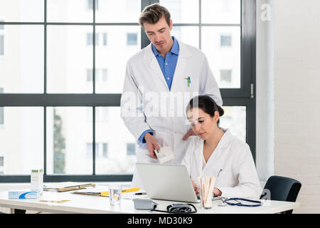 Doctor and pharmacist checking information on a laptop in a hospital - Stock Photo