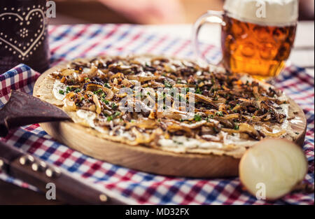 Traditional slovak potato pancake with fried onion bacon and cream with draft beer. - Stock Photo