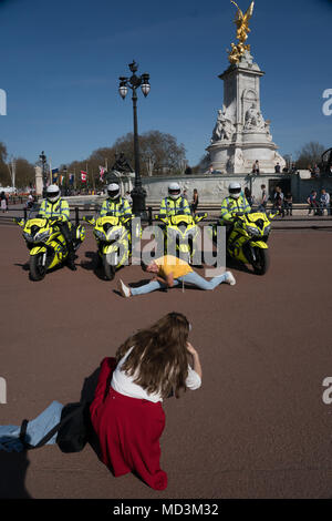 London, UK. 18th April 2018. Tourists take pictures of policemen on motorbikes in front of Buckingham Palace on a day when temperatures reached 25 degrees in London. Photo date: Wednesday, April 18, 2018. Photo: Roger Garfield/Alamy Live News - Stock Photo