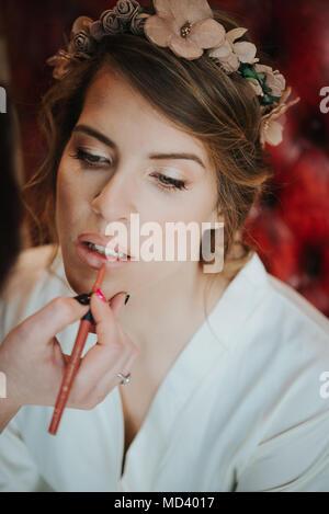 Bride having lipliner applied by make-up artist - Stock Photo