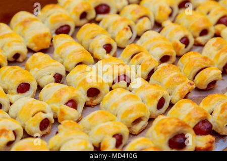 Hot dog rolled in puff pastry sausages in the dough - Stock Photo