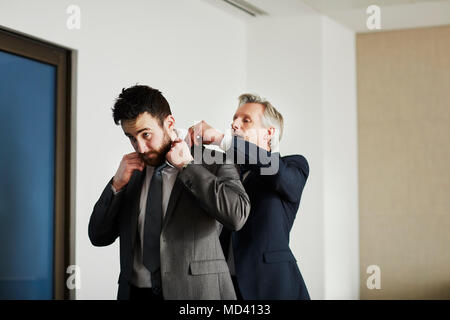 Senior businessman adjusting colleague's jacket in office - Stock Photo