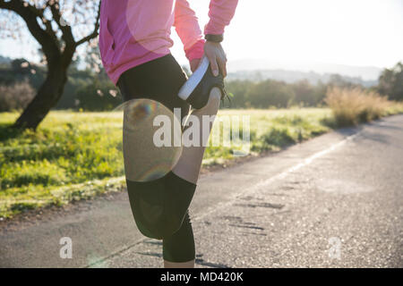 Young woman exercising in rural setting, stretching leg, low section - Stock Photo