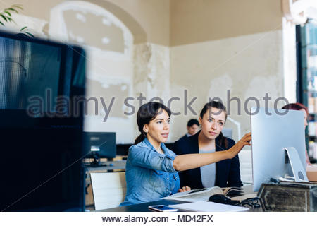 Two businesswomen sitting at desk, looking at computer screen - Stock Photo