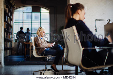 Businesspeople in office, two women sitting at desk working, businessman and woman looking out of window in background - Stock Photo