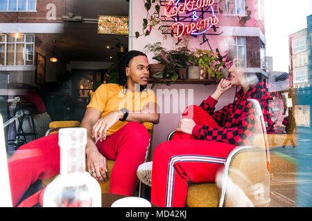 Young friends chatting in bar - Stock Photo