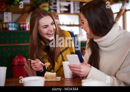 Young women smiling over text message on mobile phone - Stock Photo