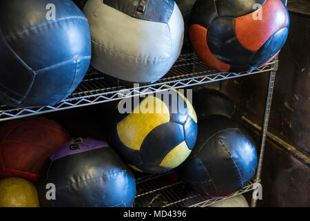 Medicine balls on metal shelf in gym, close-up - Stock Photo