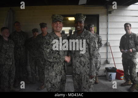 180307-N-MS236-0007 KWAJALEIN, Marshall Islands (March 7th, 2018) Captain Jeffrey Kilian, Commodore, 30th Naval Construction Regiment (NCR), left, presents a coin to Construction Electrician 3rd Class Kamerial Wall. Wall, an electrician assigned to Naval Mobile Construction Battalion (NMCB) 11, Construction Civic Action Detail Marshall Islands, was recognized for her efforts in the retrograde of a project in Ebeye. NMCB-11 is forward deployed to execute construction, humanitarian and foreign assistance, and theater security cooperation in the 7th Fleet area of operations. (U.S. Navy photo by C - Stock Photo
