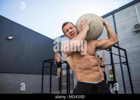 Four people exercising in gymnasium, man in foreground using atlas stone - Stock Photo