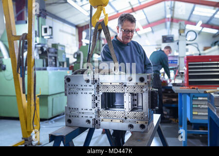 Engineer working on mould for plastic injection in precision engineering factory - Stock Photo