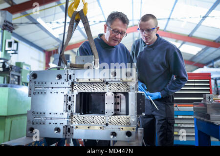 Engineer and apprentice working on mould for plastic injection in precision engineering factory - Stock Photo