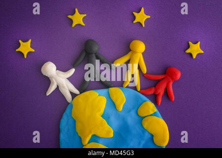 Group of people around the world. People and Earth with Stars are made out of play clay (plasticine). Close up. - Stock Photo
