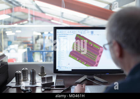 Engineer using CAD program in precision engineering factory - Stock Photo