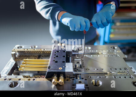 Engineer working on plastic injection mould in precision engineering factory, mid section, close up - Stock Photo