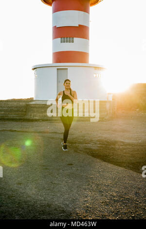 Young female runner running on coastal dirt track at sunset - Stock Photo