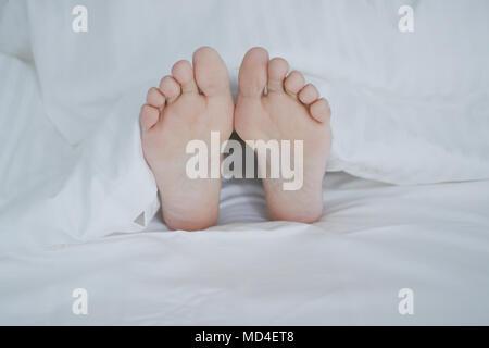 Crop female feet under blanket - Stock Photo