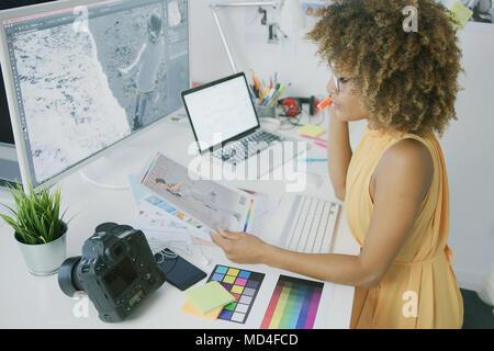 Pensive editor exploring photos - Stock Photo