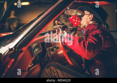 Lucky Casino Winner Kissing Red Craps Dices Inside His Classic Car. Caucasian Men in His 30s Wearing Burgundy Suite and Cowboy Hat. - Stock Photo