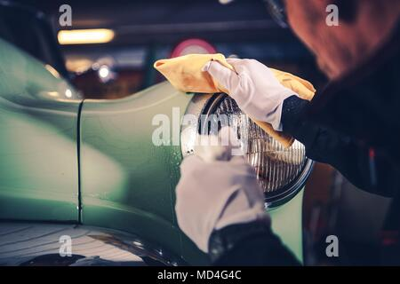 Retro Car Detailing. Classic Car Cleaning by Professional Vehicle Cleaner. - Stock Photo
