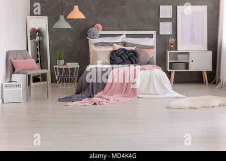 Two pink and grey blankets thrown on a bed with many pillows standing in bedroom interior - Stock Photo