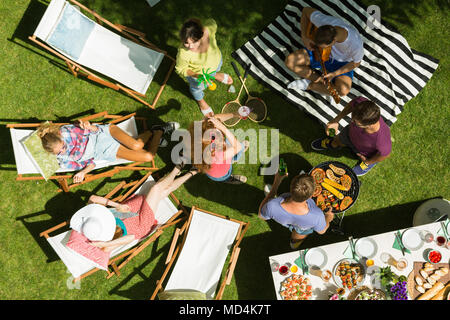 Friends having a barbeque party while relaxing in the shade