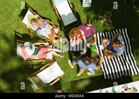 Top view of group of friends enjoying summertime garden party in the countryside, sitting on deck chairs, talking and sunbathing surrounded by nature