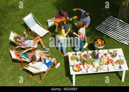 Happy young people chilling, talking and playing guitar at countryside barbecue party, friends sunbathing sitting on deck chairs - Stock Photo